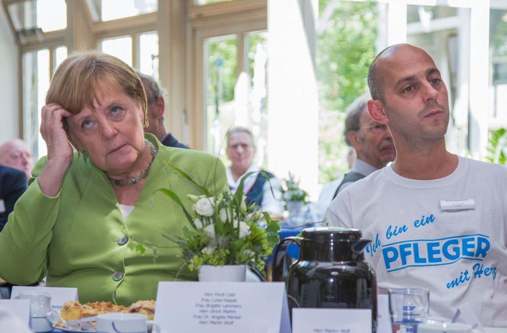 Bundeskanzlerin Angela Merkel sitzt Ferdi Cebi, Pfleger, an einer Kaffeetafel mit Bewohnern des Altenheims. Die Kanzlerin löst damit eine Zusage ein, die sie dem Pfleger in einer ZDF-Sendung im vergangenen Wahlkampf gegeben hat. Foto: dpa