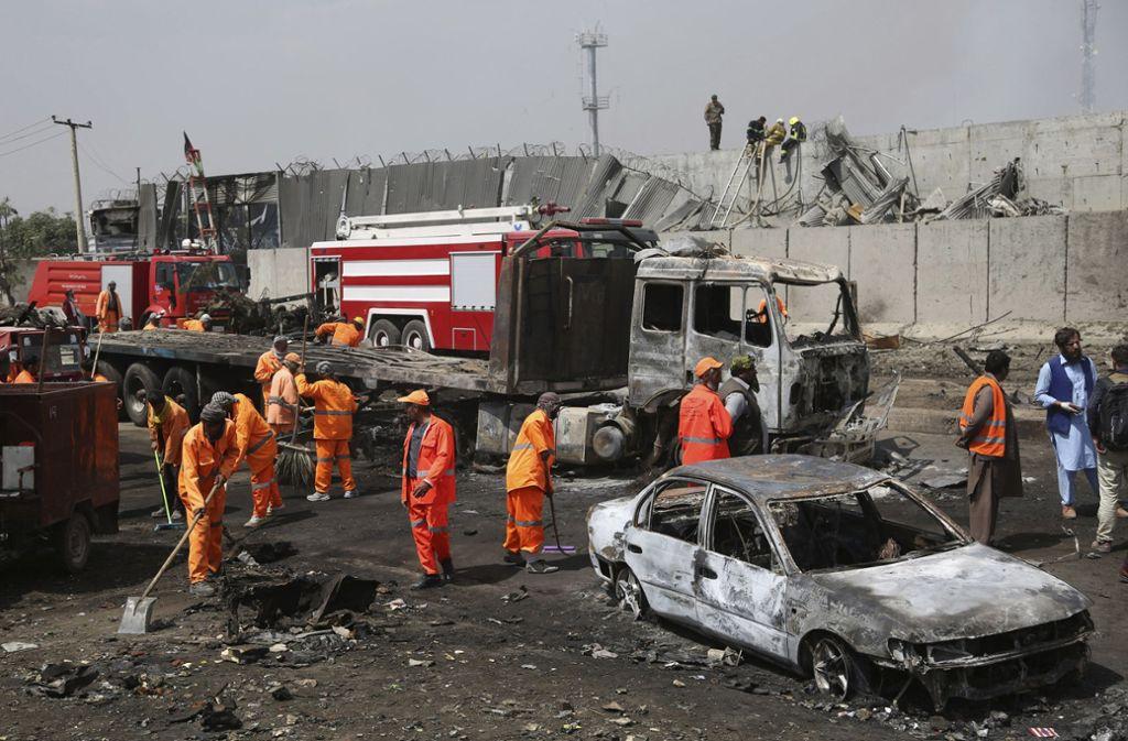 Arbeiter beseitigen Spuren des jüngsten Terroranschlags in Kabul. Im Hintergrund eine Schutzwand, mit der ein Areal ausländischer Botschaften und Organisationen abgeschirmt wird. Foto: AP