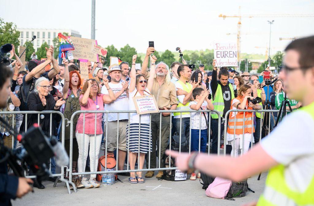 """Stuttgart: Teilnehmerinnen und Teilnehmer jubeln während einer Protestkundgebung der Initiative """"Querdenken 711"""" auf dem Cannstatter Wasen. Foto: dpa/Sebastian Gollnow"""
