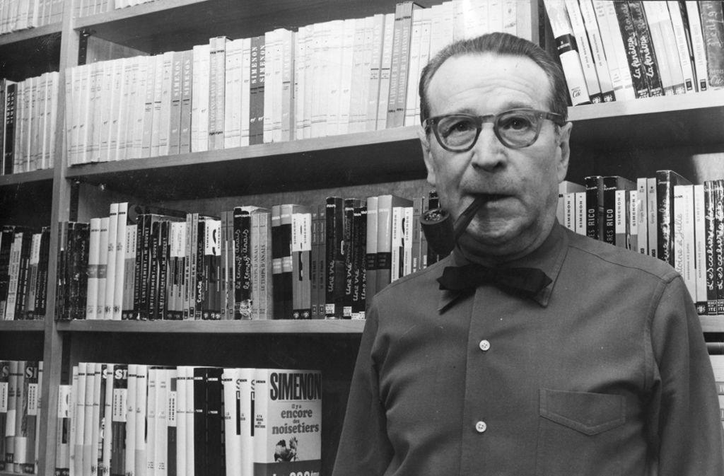 Georges Simenon (1903-1989) steht hier vor Belegexemplaren seiner Bücher – aber das Regal fasst nur einen winzigen Ausschnitt seines enormen Schaffens. Foto: Getty