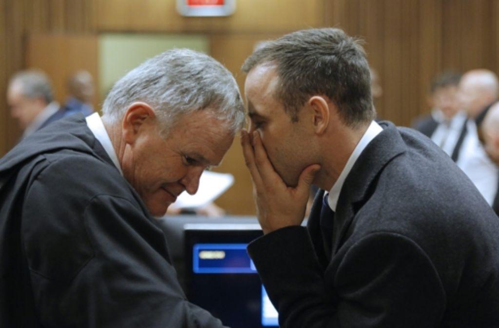 Oscar Pistorius spricht mit seinem Anwalt Barry Roux. Foto: dpa
