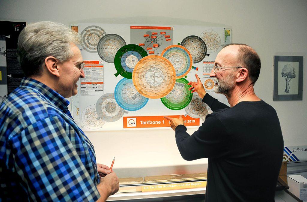 Dietmar Tatzel (rechts) und Ingo Profuß zeigen auf die neue Tarifzonenspinne im VVS. Daneben sind einige Versionen zu sehen, die sie auch entwickelt haben. Foto: Lichtgut/Max Kovalenko