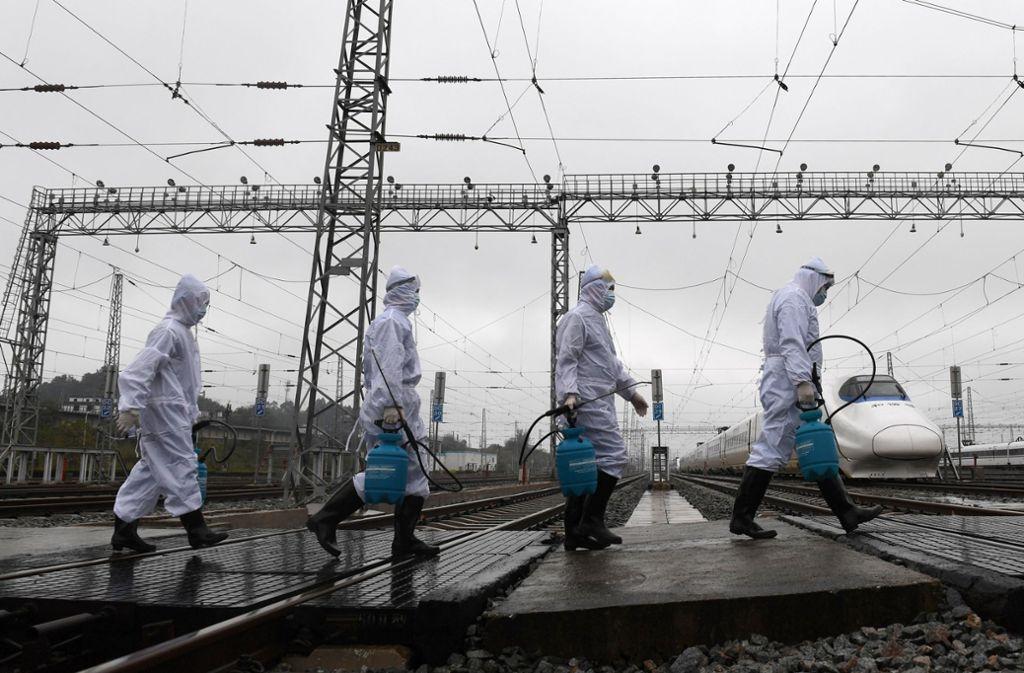 In China desinfizieren Fachleute zum Beispiel Züge, um eine weitere Verbreitung des neuartigen Coronavirus Sars-CoV-2  zu verhindern. Foto: dpa/Lu Boan