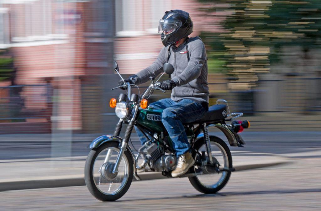 Ein Fahrlehrer fährt auf einem Simson S51 Moped. Foto: dpa