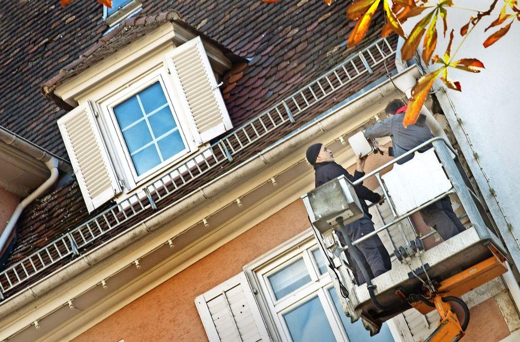 Zwei Handwerker schrauben am Cosmopolita auf dem Markplatz eine graue Sendeantenne an. Foto: Horst Rudel