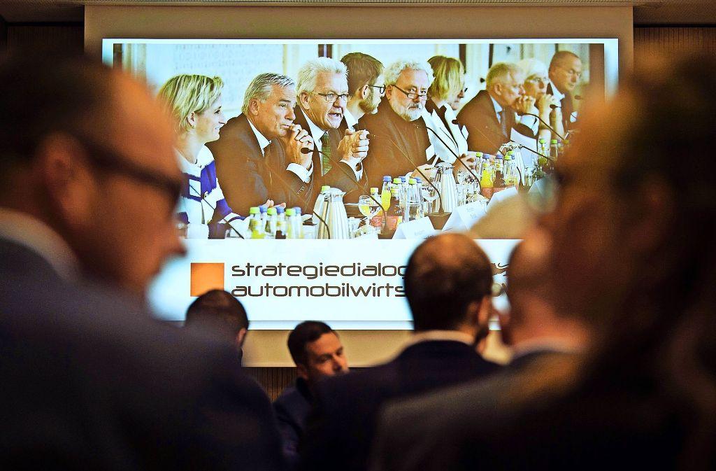 Ministerpräsident Winfried Kretschmann rechtfertigt am Dienstag vor Medienvertretern im Landtag sein Festhalten an Strategiegesprächen mit der Automobilwirtschaft. Im Hintergrund ein Transparent  von der Auftaktveranstaltung mit Firmenvertretern Mitte Mai in Stuttgart. Foto: dpa