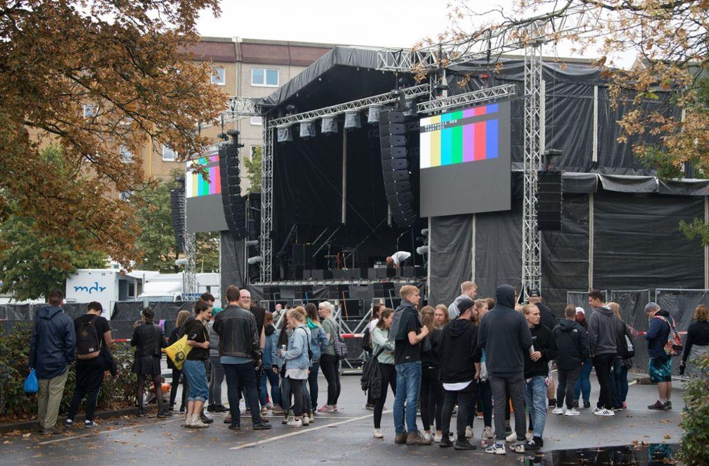 Konzertbesucher warten auf dem Parkplatz an der Johanniskirche hinter einer Absperrung vor der Bühne auf den Beginn des Konzerts. Foto: dpa-Zentralbild