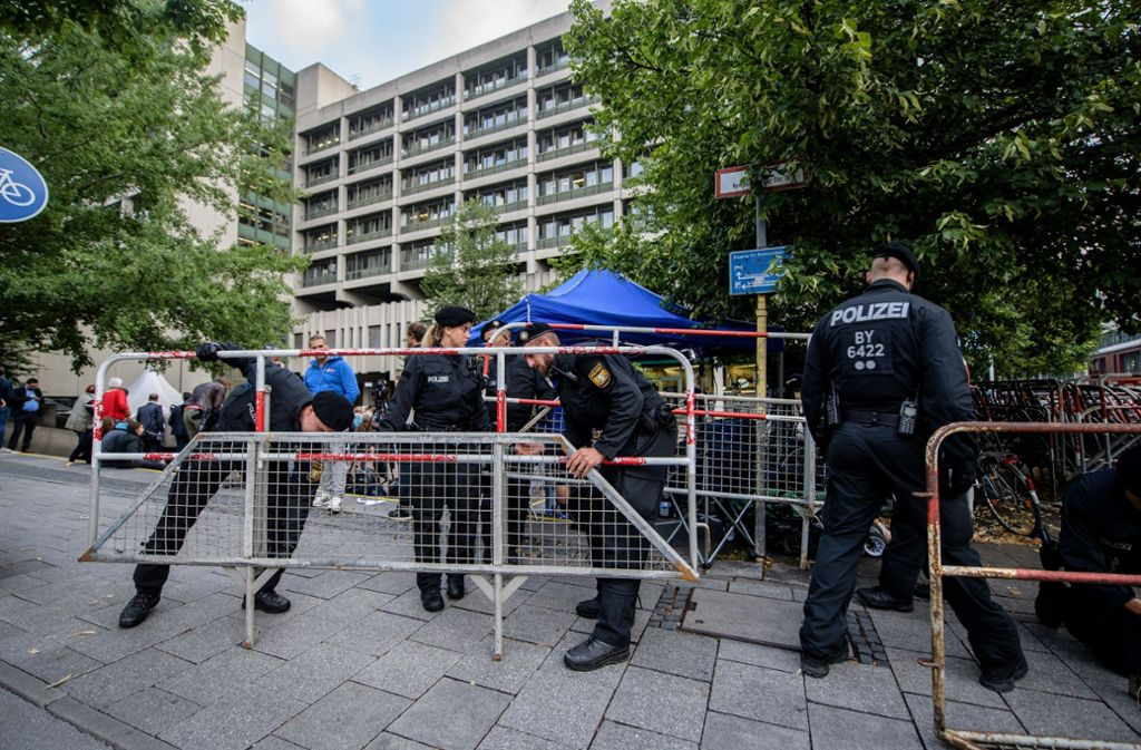 Polizisten stellen vor dem Oberlandesgericht in München Zäune auf.  Foto: dpa