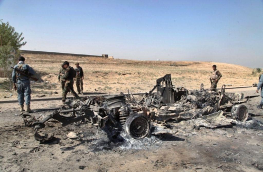 Afghanische Sicherheitskräfte inspizieren ein ausgebranntes Wrack. Foto: dpa