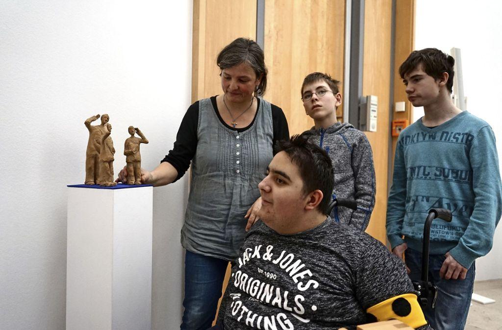 Die Schüler Marcel, Friedrich und Florian (von rechts), die die Engel aus Ton geschaffen haben, in der Ausstellung im Robert-Bosch-Krankenhaus mit  der  Ausstellungsmacherin  Claudia Ebert. Foto: Höfle (z)
