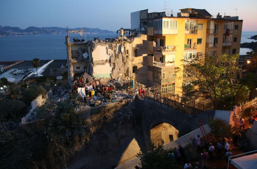 Rettungskräfte arbeiten sich am 7. Juli durch das Geröll eines zusammengestürzten Gebäudes in Torre Annunziata (Italien). Foto: dpa